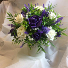 An artificial flower table centre in shades of ivory lilac & purple