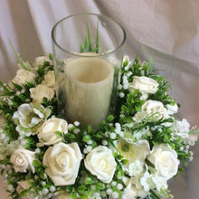 a table centre wreath of ivory artificial flowers
