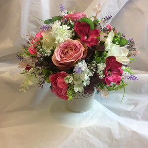 An table centre featuring artificial flowers - choice of container