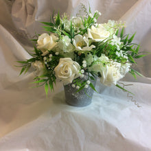 A table centre featuring artificial ivory flowers
