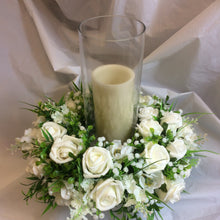 A table centrepiece of ivory flowers and foliage