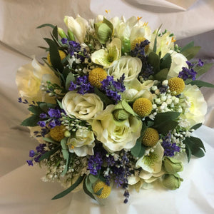 a wedding bouquet featuring dried and silk flowers