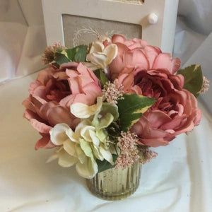silk flower arrangement in gold glass container