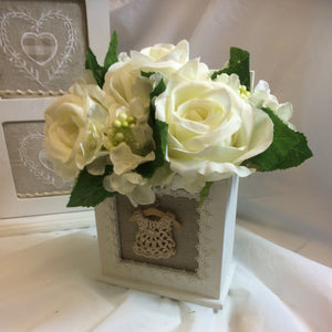 A flower arrangement of large ivory hydrangea & roses