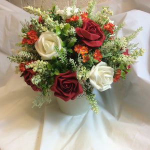 A flower arrangement of ivory orange and red flowers