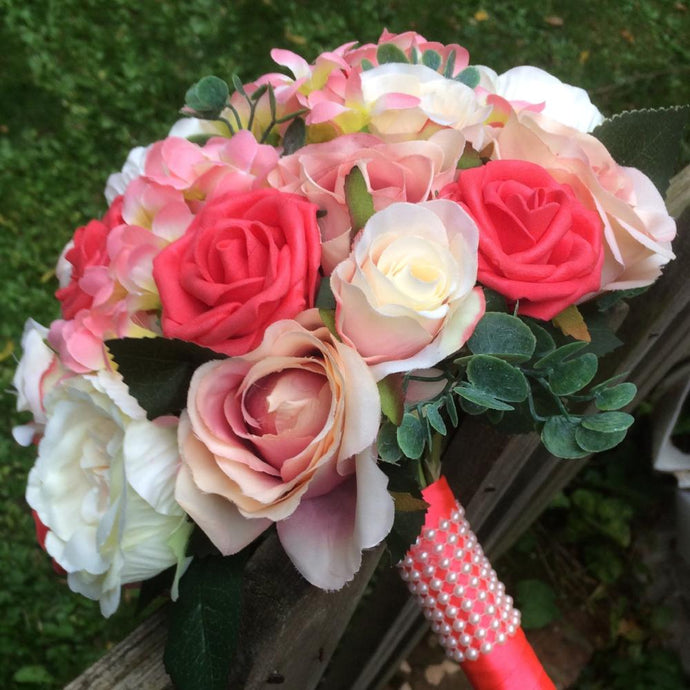 a brides bouquet of artificial coral and apricot flowers