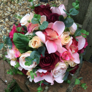 a wedding bouquet of coral and burgundy silk flowers
