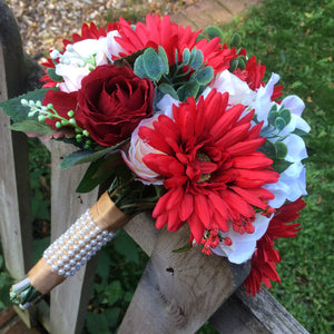 a brides wedding bouquet of artificial silk ivory, red & peach flowers
