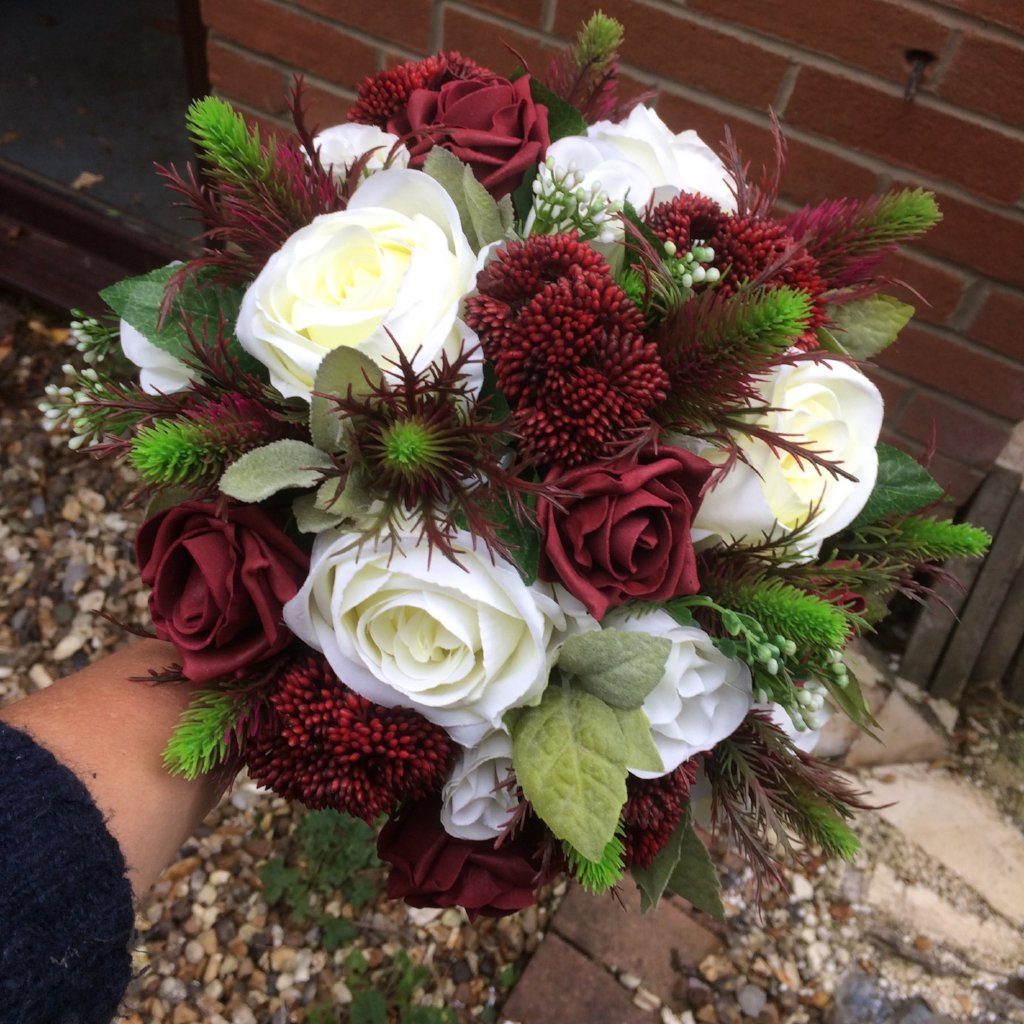 wedding bouquet of artificial flowers in shades of ivory and burgundy