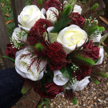A wedding bouquet featuring ivory & burgundy roses plus thistles & foliage