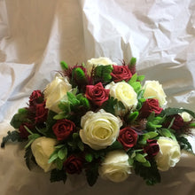 An top table flower arrangement of burgundy and ivory artificial roses and thistles