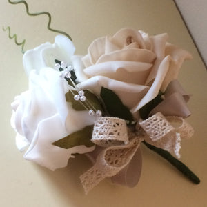 A corsage featuring foam roses in shades of champagne, ivory and latte