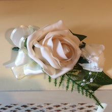 A corsage featuring foam roses in shades of ivory and latte