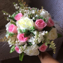 A wedding bouquet featuring silk ivory and pink roses & foliage