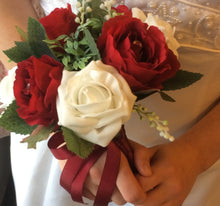 A bridesmaids wedding bouquet featuring artificial red & white roses