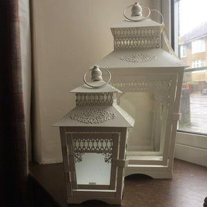 a set of two off white metal lanterns