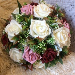a wedding bouquet of burgundy ivory and pink foam roses, hypericum and hydrangea