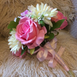A wedding bouquet of artificial ivory, lilac and pink Flowers