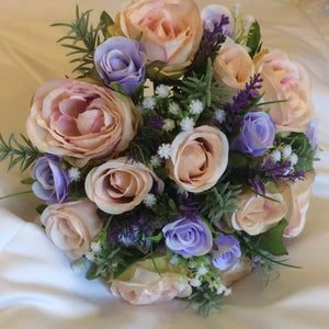 an artificial wedding bouquet of silk roses in shades of lilac and blush pink