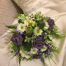 A wedding bouquet of artificial white and purple flowers