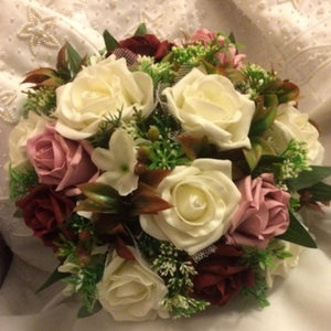 an artificial wedding bouquet of dusky pink, burgundy and ivory roses
