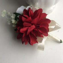 an artificial corsage featuring dahlia and roses in shades of burgundy & ivory