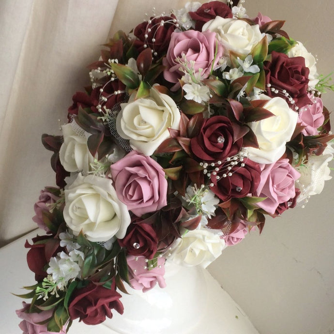 a teardrop bouquet of foam roses in shades of ivory burgundy and dusky pink