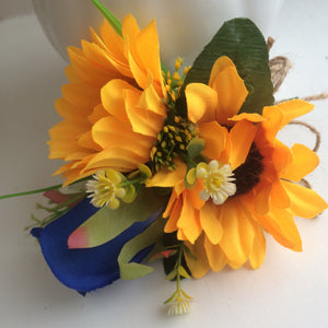 A corsage featuring two yellow sunflowers & royal blue silk rose