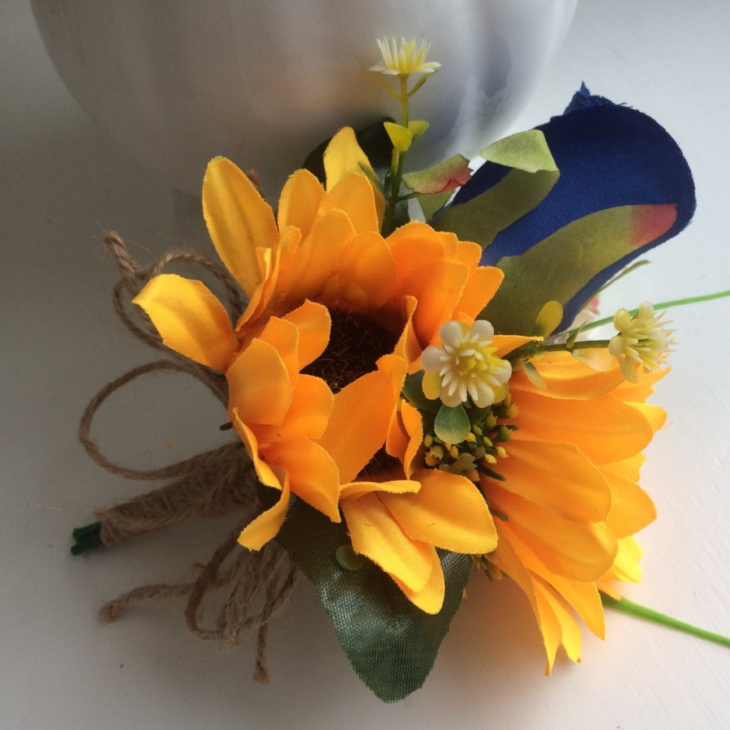 a sunflower corsage with royal blue rose