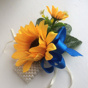 a wrist corsage of yellow sunflowers and royal blue ribbon