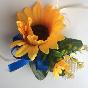 A wrist corsage featuring a yellow sunflowers on an ivory pearl bracelet
