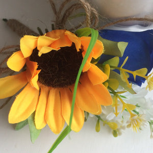 A buttonhole featuring a yellow sunflower & royal blue silk rose
