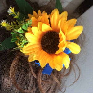 A bridal hair comb featuring yellow sunflowers & royal blue ribbon