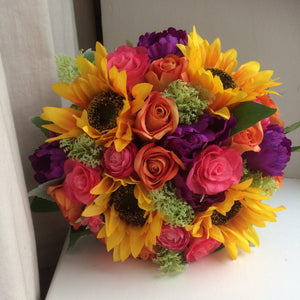 artificial wedding bouquet of purple. orange, yellow and hot pink flowers