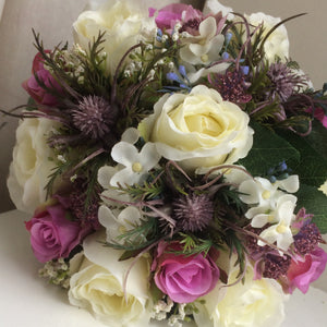 A wedding bouquet featuring artificial silk ivory & deep pink roses, thistles & foliage