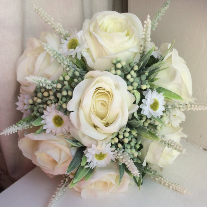 a brides bouquet of artificial ivory roses and daisies