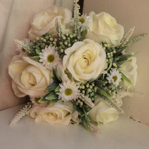A brides wedding bouquet of artificial silk ivory roses and daisies