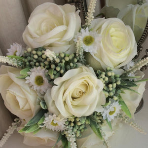 a wedding bouquet of artificial ivory roses and daisies