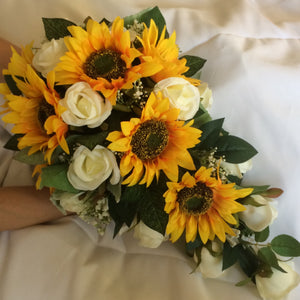 A brides teardrop bouquet of artificial ivory roses and sunflowers
