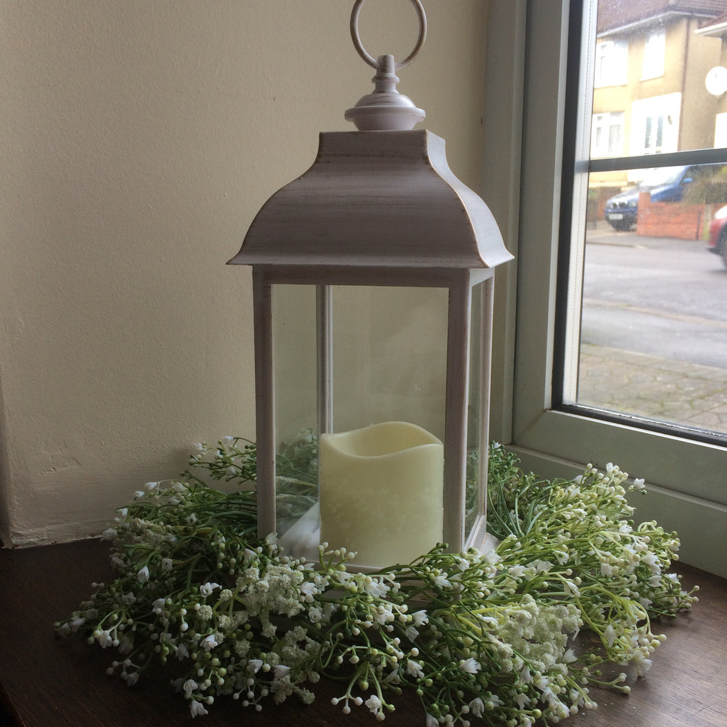 A gold brushed effect off white metal lantern with LED candle