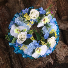 a funeral wreath of yellow and ivory/cream artificial silk flowers