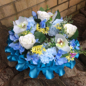 a memorial wreath of artificial blue and cream silk flowers