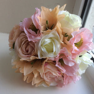 A wedding bouquet featuring peach. pale pink & ivory flowers