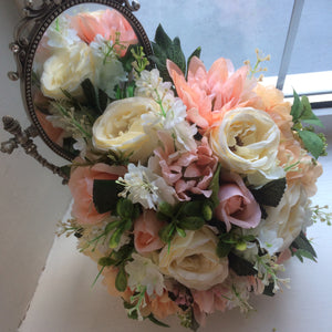 - A wedding bouquet featuring peach and cream flowers