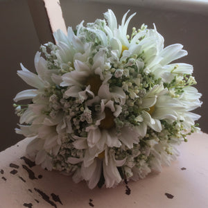 a wedding bouquet of artificial white daisies and gypsophila