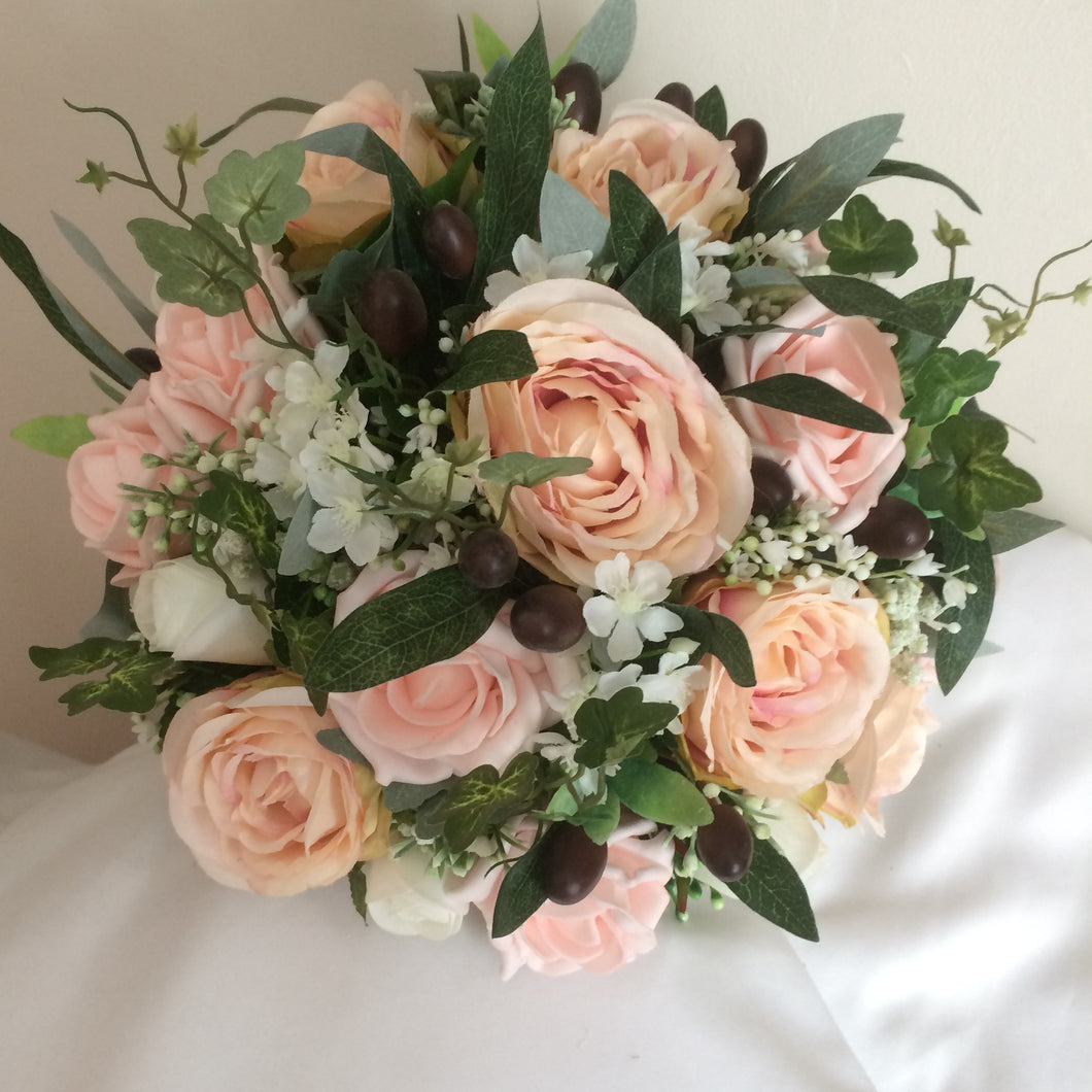 a bouquet of blush roses and olive foliage