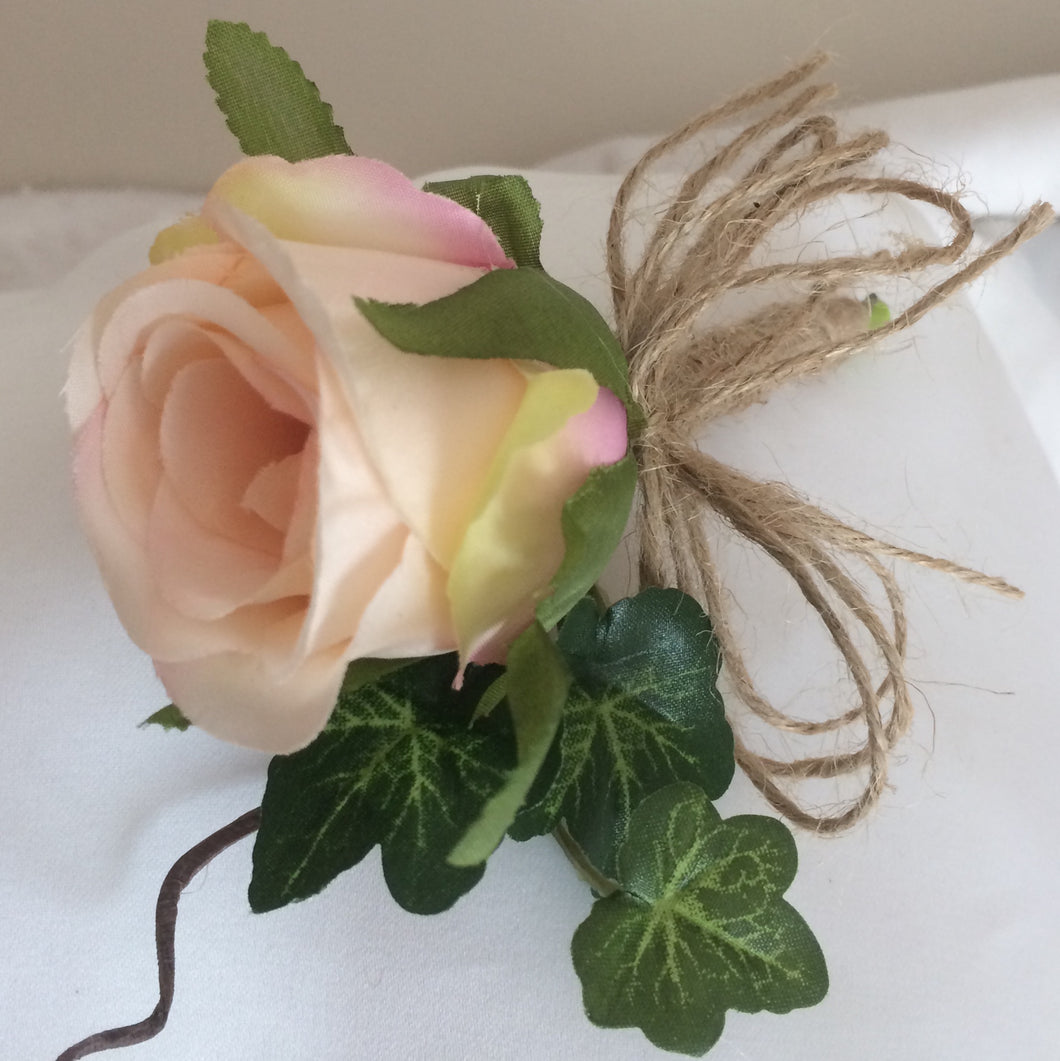 A wedding buttonhole featuring a blush pink silk rose and ivy