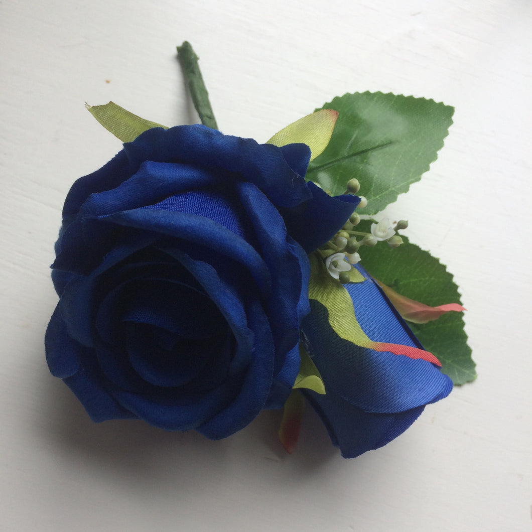 a pin on corsage of silk roses