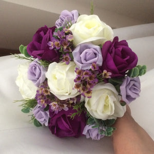 an artificial wedding bouquet of silk and foam lilac, purple and ivory roses