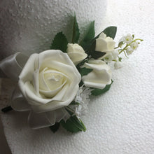 a corsage of ivory foam roses